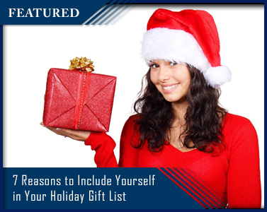 woman dressed in red with Santa hat holding present
